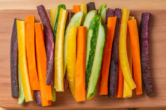 top view of colorful carrots and cucumbers vegetables julienned for snack on wooden board, concept of vegetarian appetizer