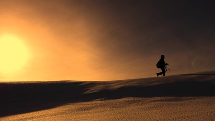 photographer traveler in winter goes on snowy ridge in rays of yellow sunset. mountaineer with camera and tripod is walking in snow along top of holom.