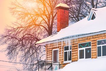 Wooden house covered with snow and icicles
