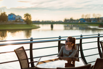 Young woman in sunglasses sitting in outdoor cafe at the table near the Wisla river at sunset. Krakow, Poland