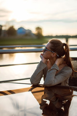 Young woman in sunglasses sitting in outdoor cafe at the table near the Wisla river at sunset and enjoying the view. Krakow, Poland