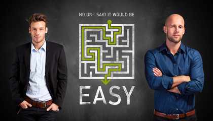 two businessmen in front of a blackboard with a shortcut to through maze