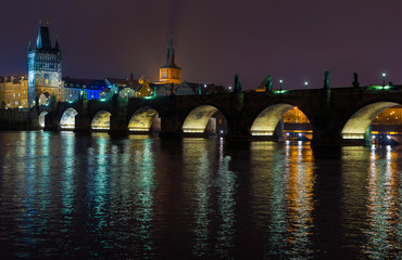 Night view of the Charles Bridge in Prague, Czech Republic. River, old town bridge tower and old town water tower