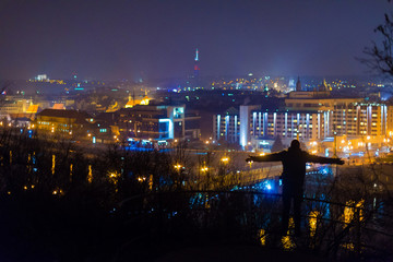 Man silhouette standing on the hill with beautiful view of night city. Prague, Czech Republic