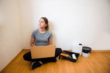 Portrait of young beautiful woman sitting with laptop while painting new apartment, renovating the room. Looking for ideas, watching tutorials