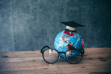 Graduation cap on globe model with glasses on wooden desk for concept education and scholarships.