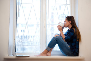 Young woman in casual denim clothes sitting on the window sill and drinking coffee or tea. Girl sitting near the window and dreaming