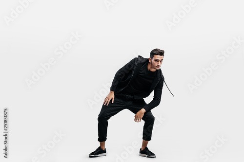 fbaa9e5f Handsome young man dressed in a sport black clothes is dancing street dance.