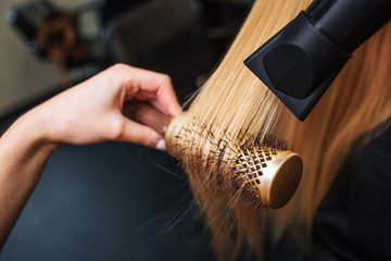 Close-up of hairdressers hand drying blond hair with hair dryer and round brush. Doing hairstyle in beauty salon