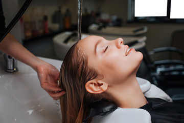 Side view of beautiful young woman with closed eyes smiling while hairdresser rising hair after shampoo. Hair spa in beauty salon
