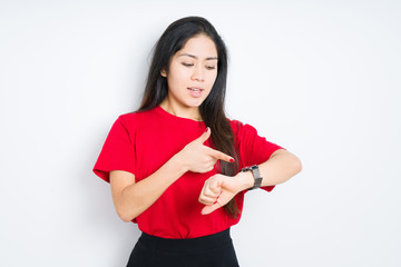 Beautiful brunette woman wearing red t-shirt over isolated background In hurry pointing to watch time, impatience, upset and angry for deadline delay