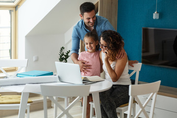 Happy family in living room. Mother works from home ,while her husband and daughter support her .
