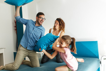 Family making fun and fight with pillows in bed room.