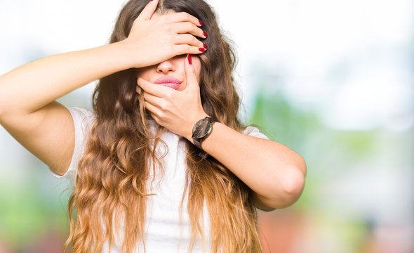 Young beautiful woman wearing casual white t-shirt Covering eyes and mouth with hands, surprised and shocked. Hiding emotion