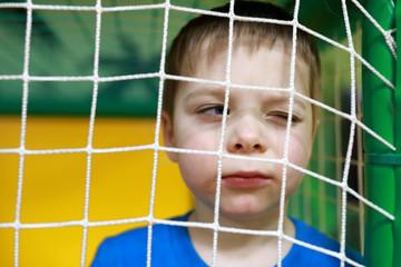 Boy behind net
