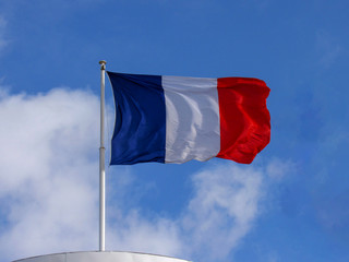French Tricolor fabric material flag flying in the high wind with copy space with blue sky background