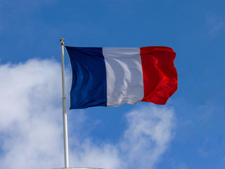 Traditional texture fabric tricolor French flag waving in the wind with natural blue sky background
