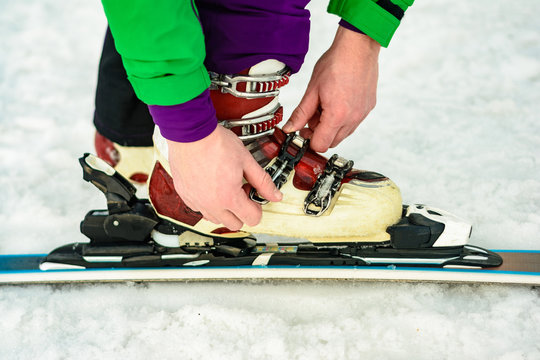 The skier wears footwear for skiing and fixes the fastener