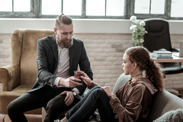Bearded counselor bringing glass of water to nervous teenager