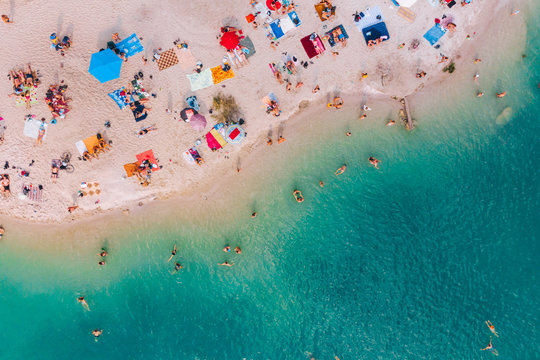 aerial view of sunny sandy beach with blue azure water