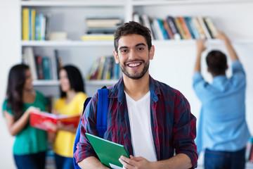 Lachender spanischer Student in der Uni-Bibliothek