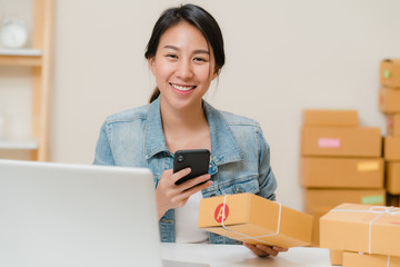Beautiful smart Asian young entrepreneur business woman owner of SME checking product on stock scan qr code working at home. Small business owner at home office concept.