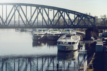 Big river touristic cruise ships overview with the bridge on background