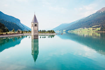 Fototapete - The old bell tower of Curon Venosta church rising out of the waters lake of Resia.