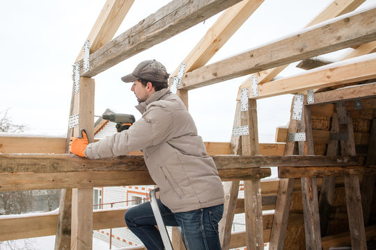 Carpenter using electric screwdriver. Man builds a roof of wooden planks. Attic renovation. Building construction outdoor. Countryside house. Farm householding.