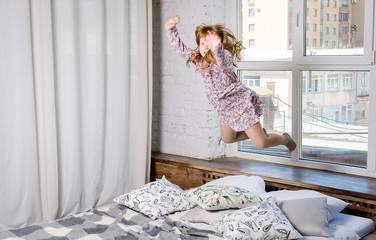 8452ea3b52 Happy little girl jumping on bed. Happy and carefree childhood