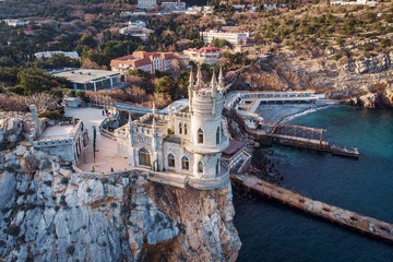 Swallow Nest aerial drone shot, ancient castle on top of mountain cliff near sea Yalta region, Crimea. Beautiful famous palace architecture and amazing nature landscape