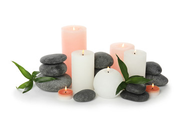 Beautiful spa composition with candles and stones on white background