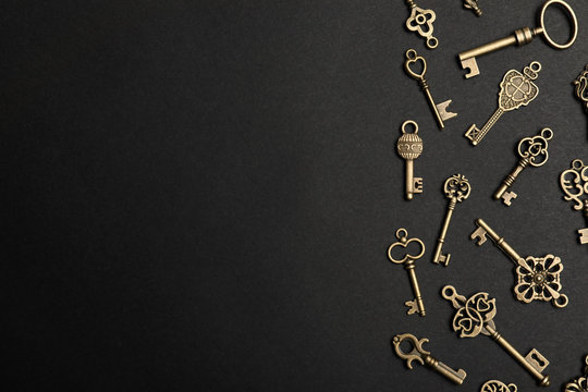 Flat lay composition with bronze vintage ornate keys on dark background, space for text
