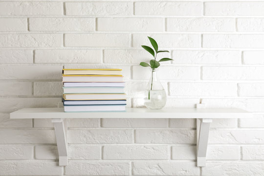 Shelf with stack of hardcover books hanging on brick wall