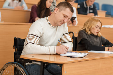 Disable man in wheelchair sitting in lecture hall, listening teacher and writing notes at university. Male adult studying and getting high education. Concept of equality and available learning.