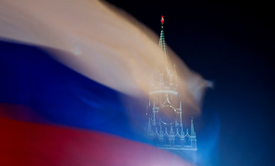 Russian flag flies with the Spasskaya tower of Moscow's Kremlin in the background in Moscow