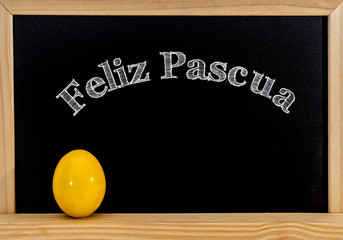 Easter frame with painted eggs and chalkboard. Happy Easter in white chalk. Happy Easter in spanish : feliz Pascua