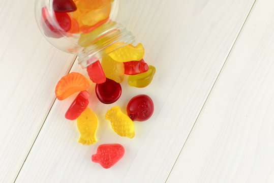 colored gummy fruit candy spilled, on a white wooden table