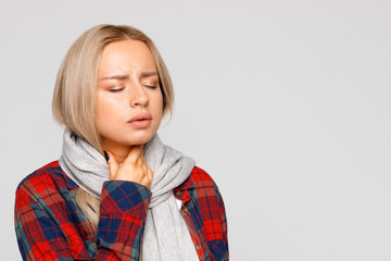 Portrait of upset young woman in checked shirt, wrapped scarf  having sore throat, holding hand on her neck.Throat pain, painful swallowing,   tonsillitis, upper respiratory tract diseases concept