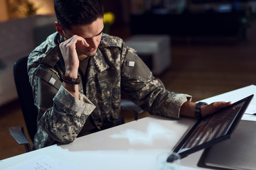 Sad army soldier looking at American flag in picture frame.