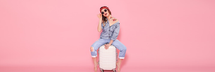 Beautiful young girl in denim shirt with water decal tattoo flowers sticker smiling and sitting on suitcase