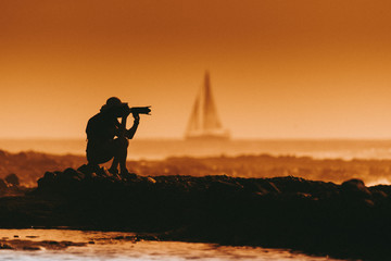 Silhouette of a photographer at the sunset sitting near the sea. Man with photo camera taking pictures at the beach. Sail boat in the background Orange sky and waves. Summer vacation evening landscape