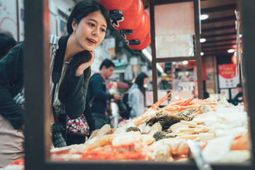 vintage picture of young asian girl photographer picking many seafood sold in Kuromon market in Osaka Japan. chinese woman traveler picking choosing in vendor in black door ichiba osaka japan.