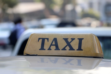 Taxi light sign or cab sign in brown color with black text on the car roof.