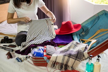 Obraz Woman hand packing a luggage for a new journey and travel for a long weekend. - fototapety do salonu