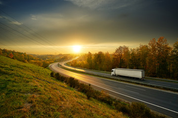 Fotobehang - White truck driving on the asphalt highway winding through autumn landscape at sunset