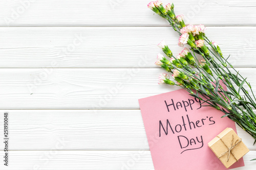 Happy Mother's Day concept. Hand lettering near bouquet of pink carnation and gift box on white wooden background top view space for text
