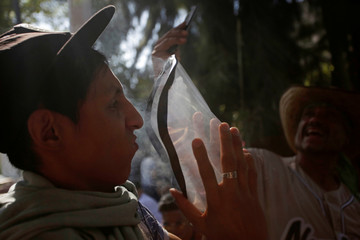 A participant smokes marijuana in a makeshift bong during a march in support of the legalization of marijuana in Mexico City