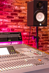 audio mixing console and monitor speaker in recording studio, copy space on brick wall. recording, post production, broadcasting concept