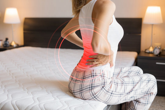 Woman suffering from back pain because of uncomfortable mattress